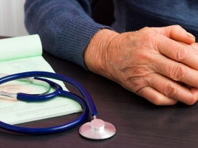 An elderly person's hands on a doctor's desk next to a stethoscope, photo by Barabas Attila/Fotolia