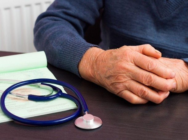 An elderly person's hands on a doctor's desk next to a stethoscope