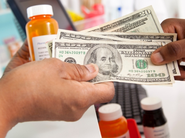 Woman paying cash for prescription medications at pharmacy