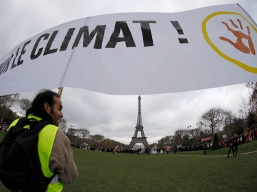 """Environmentalists hold a banner which reads in part, """"For the Climate,"""" near the Eiffel Tower during the World Climate Change Conference 2015"""