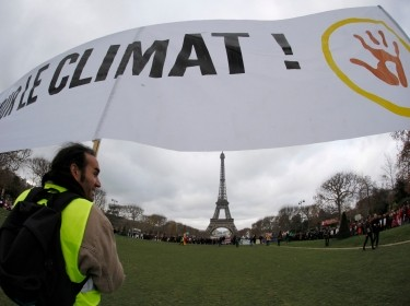 "Environmentalists hold a banner which reads in part, ""For the Climate,"" near the Eiffel Tower during the World Climate Change Conference 2015"