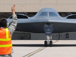 A 509th Aircraft Maintenance Squadron crew chief marshals a B-2A Spirit bomber during an orientation flight at Whiteman Air Force Base, Mo., May 27, 2015