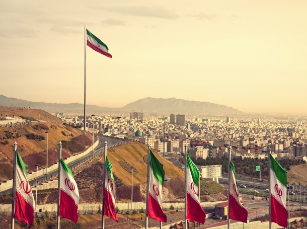 A row of Iranian flags in front of the Tehran skyline