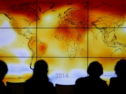 Participants are seen in silhouette as they look at a screen showing a world map with climate anomalies during the World Climate Change Conference 2015 (COP21) at Le Bourget, near Paris, France, December 8, 2015