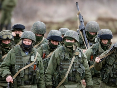 Uniformed men, believed to be Russian servicemen, march outside a Ukrainian military base, March 5, 2014