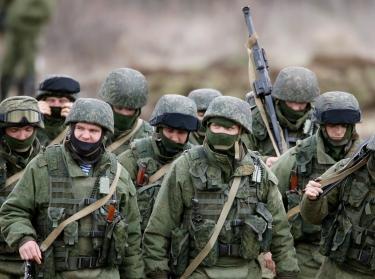 Uniformed men, believed to be Russian servicemen, march outside a Ukrainian military base, March 5, 2014