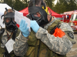 Two Oregon Army National Guard members make notes from the edge of the blast zone after a simulated dirty bomb detonated during an exercise in Portland, October 16, 2007