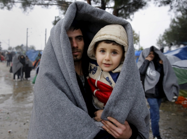 A Syrian refugee carries his son through a rainstorm at the Greek-Macedonian border near the Greek village of Idomeni, November 27, 2015
