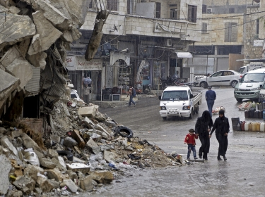 Civilians walk past a damaged building in the rebel-controlled area of Maaret al-Numan town in Idlib province, Syria, October 28, 2015
