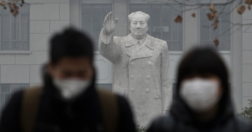 People wearing masks walk in front of a statue of the late Chinese leader Mao Zedong on a hazy day in Shanghai, December 26, 2013