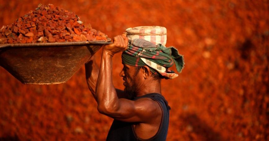A laborer lifts a basket of crushed bricks at a construction site in Dhaka, Bangladesh, May 22, 2014