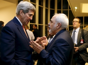 U.S. Secretary of State John Kerry talks with Iranian Foreign Minister Mohammad Javad Zarif after the IAEA verified that Iran has met all conditions under the nuclear deal, January 16, 2016, photo by Kevin Lamarque/Reuters