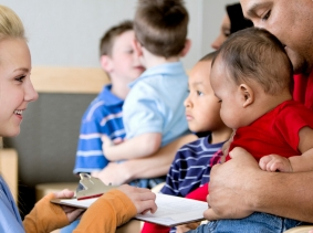 A man with his children in a doctor's waiting room, photo by nicolesy/iStock