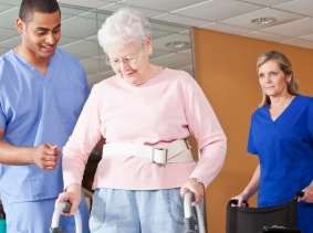Medical staff helping senior woman walk with a walker, photo by Susan Chiang/iStock