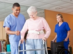 Medical staff helping senior woman walk with a walker