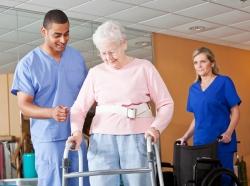 Medical staff helping senior woman walk with a walker