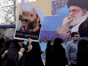 A protester holding a picture of Shi'ite cleric Sheikh Nimr al-Nimr, who was executed in Saudi Arabia, walks past a picture of Ayatollah Ali Khamenei during a rally in Tehran January 8, 2016, photo by Raheb Homavandi/Reuters