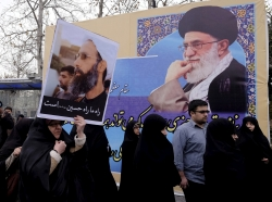 A protester holding a picture of Shi'ite cleric Sheikh Nimr al-Nimr, who was executed in Saudi Arabia, walks past a picture of Ayatollah Ali Khamenei during a rally in Tehran January 8, 2016