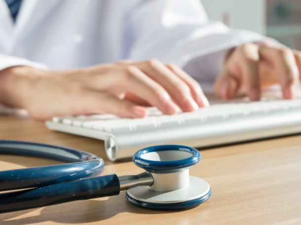 A doctor typing on a computer keyboard