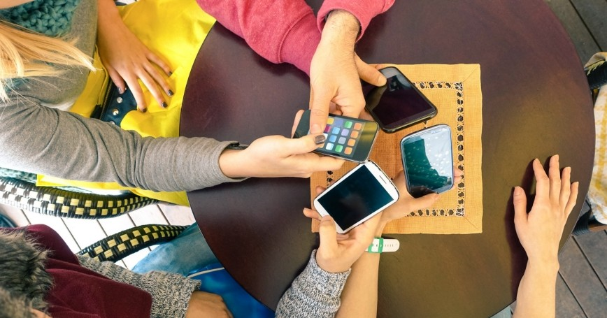 Group of friends holding their smart phones
