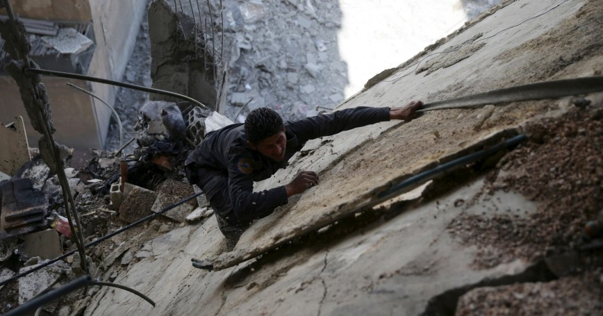 A civil defence member works at a site after airstrikes by pro-Syrian government forces in the rebel held Douma neighborhood of Damascus, Syria, February 14, 2016