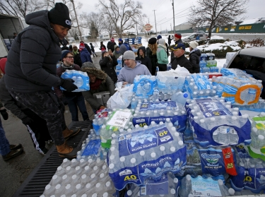 Volunteers distribute bottled water to help combat the effects of the contaminated water crisis in Flint, Michigan, March 5, 2016