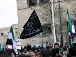 Protesters carry Al-Qaeda flags during an anti-government protest in the town of Marat Numan in Idlib province, Syria, March 11, 2016