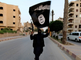 An ISIS militant waves an ISIS flag in Raqqa, Syria, June 29, 2014, photo by Stringer/Reuters