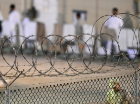 A Navy guard patrols Camp Delta's detainee recreation yard during the early morning at Guantánamo Bay naval base on July 7, 2010