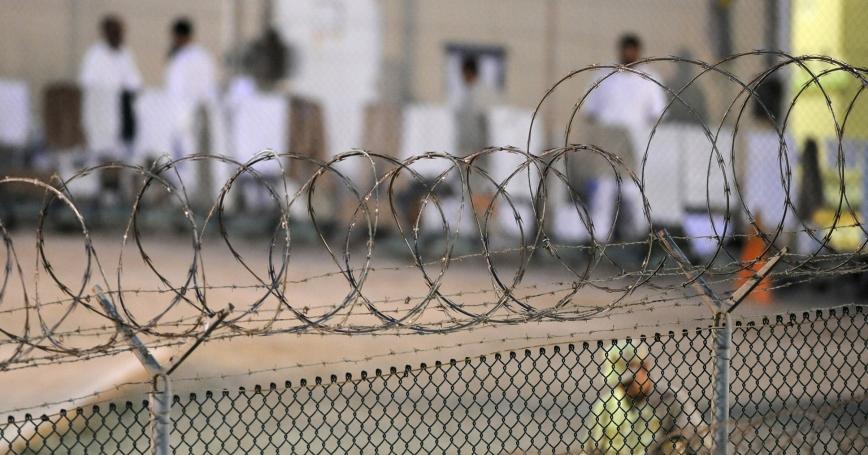 A Navy guard patrols Camp Delta's detainee recreation yard during the early morning at Guantánamo Bay naval base on July 7, 2010