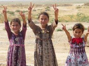 Iraqi girls gesture peace signs after Iraqi security forces entered the town of Amerli, September 1, 2014, photo by Stringer/Reuters