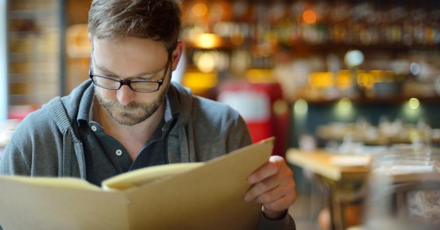 Man in a restaurant looking at a menu