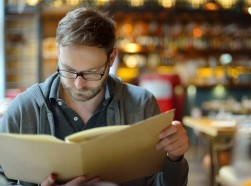 Man in a restaurant looking at a menu