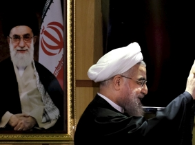 Iranian President Hassan Rouhani waves next to a portrait of Iran's Supreme Leader Ayatollah Ali Khamenei at the Interior Ministry in Tehran, December 21, 2015, photo by Raheb Homavandi/TIMA/Reuters