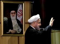 Iranian President Hassan Rouhani waves next to a portrait of Iran's Supreme Leader Ayatollah Ali Khamenei at the Interior Ministry in Tehran, December 21, 2015