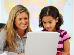 A teacher and student in a classroom looking at a laptop