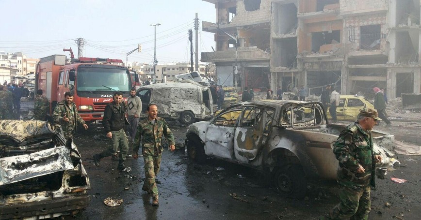 Syrian army soldiers inspect the site of a two bomb blasts in the government-controlled city of Homs, Syria, on February 21, 2016