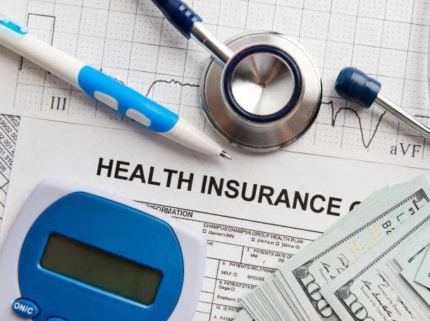 Health insurance form, U.S. currency, stethoscope