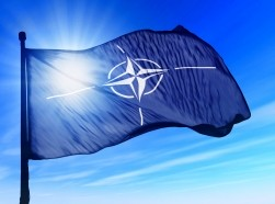 The NATO flag flies on a sunny day
