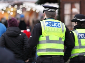 Two UK police in high-visibility jackets at an outdoor event, photo by Brian Jackson/Fotolia