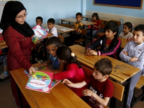 A Syrian refugee teacher distributes books to her refugee students in the Karapurcek district of Ankara, Turkey, photo by Umit Bektas/Reuters