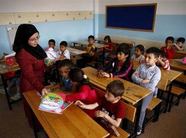 A Syrian refugee teacher distributes books to her refugee students in the Karapurcek district of Ankara, Turkey