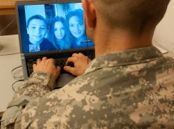A soldier deployed in Iraq video chats with his wife and children