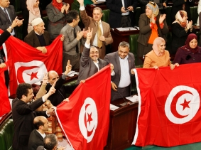 Members of the Tunisian parliament wave flags after approving the country's new constitution in Tunis, January 26, 2014, photo by Zoubeir Souissi/Reuters