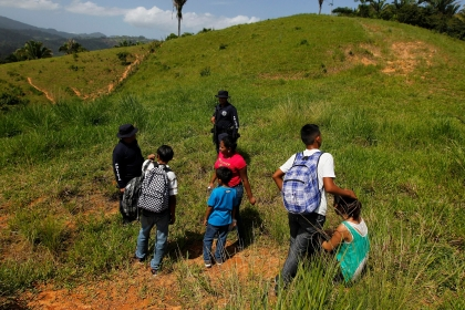 Unaccompanied minors and a family stand next to Honduran border policemen after being detained at a porous border known as La Montanita, on the border of Honduras with Guatemala, June 20, 2014