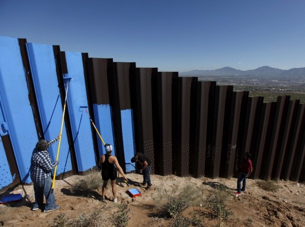 Artist Ana Teresa Fernandez and members of cultural organization Border/Arte paint the fence between Mexico and the U.S. to give it the illusion of transparency in Ciudad Juarez, Mexico, April 9, 2016