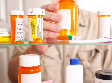 Man taking pills out of a medicine cabinet