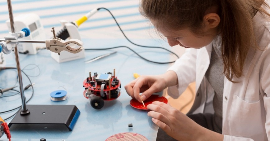 Student solders and adjusts electronic device