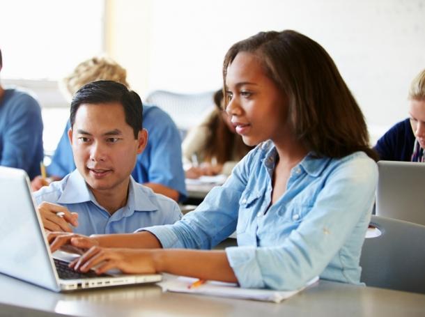 A teacher helps a high school student work on a laptop