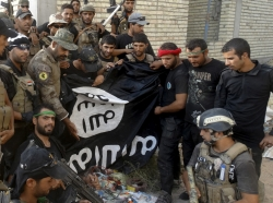 Iraqi security forces hold an ISIS flag that they pulled down at the University of Anbar, in Anbar province, July 26, 2015
